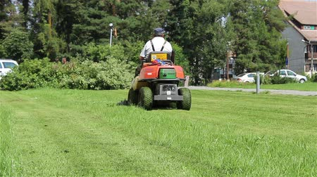 ágak : A gardener driving a lawnmower on the lawn in front of a public building.