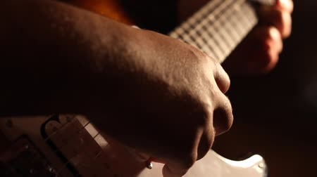 fingertips : Long shadows of the spotlight reshape on the guitar pickups, while a musician is performing on.