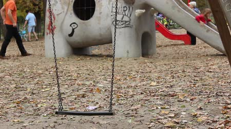 be sad : A fresh swing left swaying  in the childrens playground in the park. Can be used as video methaphor for the missing child, the unborn, the no child situations. etc.