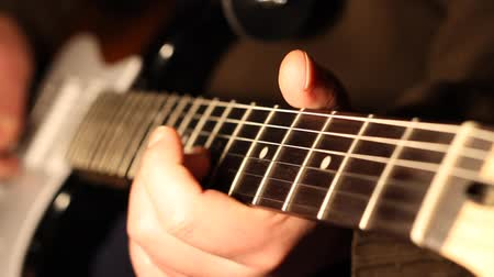 rock music : Man playing on electric guitar, shot with small depth of field, focusing on the musician fingers and guitar neck.
