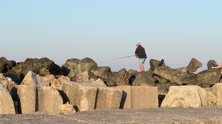 szczupak : A fisherman pay attention to rod and spin the reel, in a sunny afternoon, standing on the rocky shore of sea. Wideo