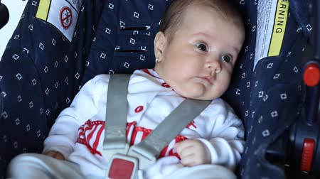 restraint : Little baby girls is seating on a Child safety seat. Child safety seats sometimes referred to as an infant safety seat, a child restraint system, a restraining car seat, or ambiguously as car seats are seats designed specifically to protect children from