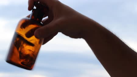 homeopatia : Old mysterious liquid, on a thick handmade old brown bottle, is easily mixed by hand. Suitable video for antique chemistry, magic potions, cures, treatments or medicine, drugs preparations.