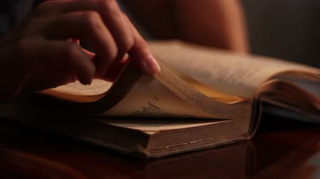 philosopher : A girl reads an old book and also plays with fingers its pages as a reading habit.