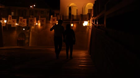 средневековый : Young couple takes a romantic walk, an night, on the old medieval downtown. Стоковые видеозаписи