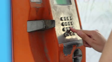 call out : A damaged rusty telephone booth, in which a person is trying to make a call. A rise in vandalism in certain regions has prompted several companies to manufacture simpler booths with extremely strong pay-phones.