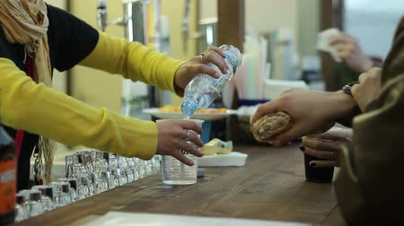 literário : Waiter fill a plastic glass with carbonated water to a customer.