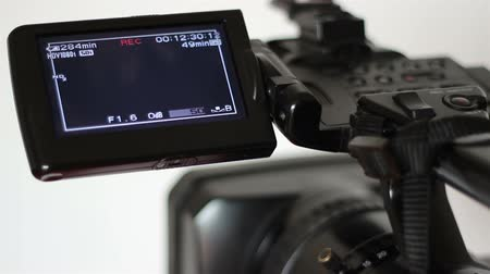 videocamera : A professional camera on the tape, is recording. Display view shot with manual commands on, and running.
