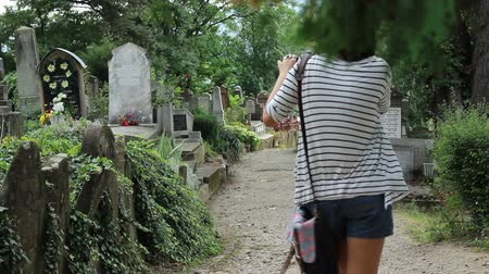 churchyard : A girl study and takes pictures of the tombstones in the old cemetery. Stock Footage