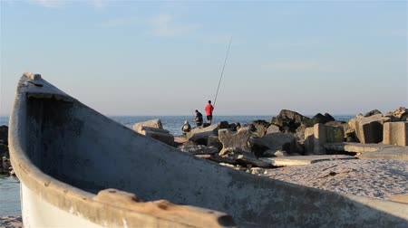 sál : Fishermen are preparing the fishing rod, at shore in sunset time. Stock mozgókép