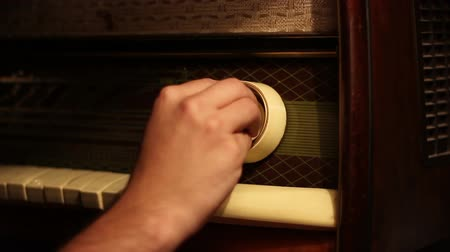 radio wave : Searching for radio stations on a vintage wooden case big radio machine. Can be used with your soundtrack creating a real feel radio tune on your  music. Shoot in a warm light of a floor lamp. Stock Footage