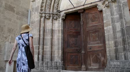 bater : A woman steps into a  Middle Ages building through a stone build portal and old wooden door. Stock Footage