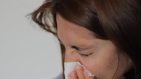 nariz : Woman with a flu is blowing her nose using a napkin.