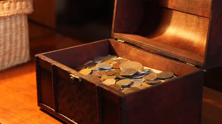 tesouro : On warm lights evening, a woman opens an old wooden box full of coins and cash value, possible some old earnings.