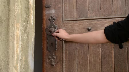 drzwi : Woman push the wrought iron door handle and opens an old wooden door. After door is left open for entering. Can be used as a metaphor for hint an a new way, a start of something era, chapter, story, ideas, facts, phenomena, etc. A new door is open, anothe Wideo
