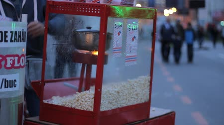 попкорн : Public place outdoors popcorn machine and vendor on a summer afternoon fiesta.