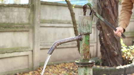 poça de água : Person using a mechanical pump for suction fresh water. Hand pumps are manually operated pumps Stock Footage