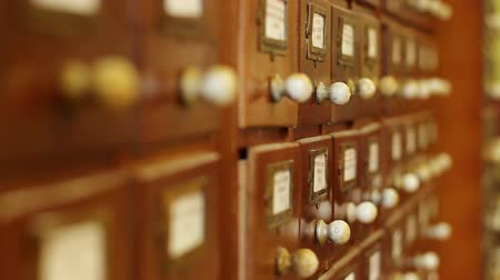 papeteria : Moving focus over rows of old wood drawers with archives files, until the right drawer handle, which fits suggest where to find the information you need, according the plot in case you edit a story short films, feature, documentary, etc.