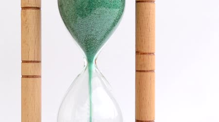 ampulheta : A lower bulb sand clock fill with green sand, on a white background. Suitable for out of time complete time illustration. Stock Footage