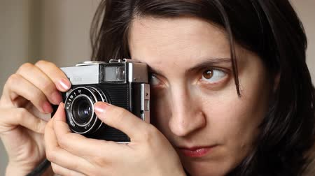 um objeto : Girl is setting the exposure and aperture on a retro photo camera. The size of the aperture and the brightness of the scene controls the amount of light that enters the camera during a period of time, and the shutter controls the length of time that the l