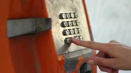 deteriorated : A girl picks up the phone, from a public cheap rusty phone booth,  dials the number, and after no one respond to her call, hangs up. Stock Footage