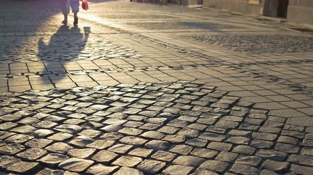 parke taşı : Long shades of walking  people in the late afternoon shaping along the cobblestone street.