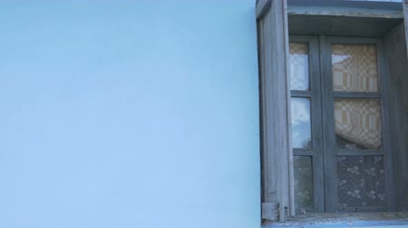 чулан : Pan shot to a blue adobe house with an ancient wooden windows with weathered shutters.