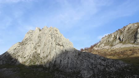 dik : Over a sharp crest of a large cliff clouds pass smootly, on blue sky. Stok Video