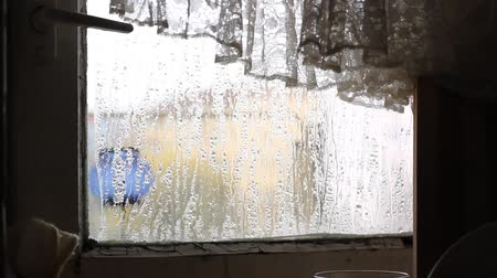 cseppfolyósítás : Condensation on glass of an old degraded window frame. Suitable video for coldness, cold and winter coming, frost, icy, low temperature, poor living conditions, misery homes, and other subjects. Stock mozgókép