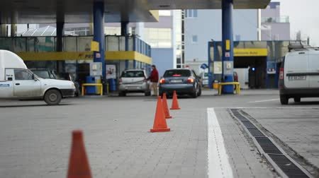 literário : Cars and people at the filling station wait in line to pump to refuel with combustible. Suitable video for a wide range of subjects like global economy, petrol price, crisis, national finances, engine technology, environment protection, green technology,  Stock Footage