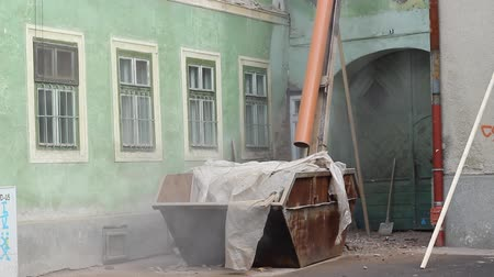 restaurálás : Debris from the construction of an old roof is shed through a  large slide tube into a container, so the process is quick and efficient.