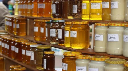 drizzler : Healthy honey products on the local orgnaic market day with jars filled with  natural honey, for sale. Stock Footage