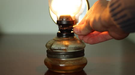 lampa naftowa : Hand is adjusting the amount of gas on old kerosene lamp.