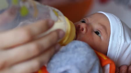 smoczek : Little infant is suckling eagerly milk from the baby bottle.