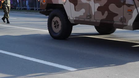 palce : 4 wheels drive military vehicle passing slowly on concrete street. This automonbile uses independent suspensions and portal geared hubs similar to portal axles to make for a full 16 inches of ground clearance. The vehicle also has disc brakes on all 4 whe
