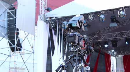 videocamera : Proffesional television with control camera forlive transmission video camera, on tripod, is ready for shooting live a music concert. In background can be seen the stage set and stage lights. Stock Footage