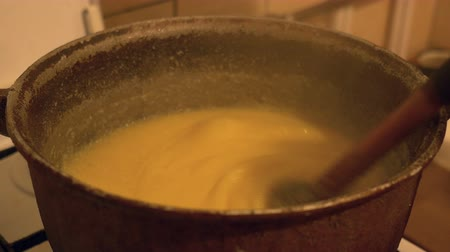 gruel : Mixing and boiling a traditional polenta in iron cauldron.