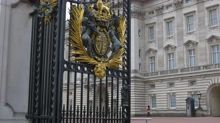 brasão : Open gates at the Buckingham Palace with Queens guards in the background.