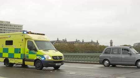 ambulância : Emergency ambulance in London in running fast to an accident, near the parliament House.