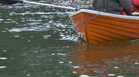 Строки : A orange boat is slipping on the waters gently to the shore. Стоковые видеозаписи
