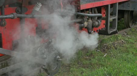 iron pipe : Steam is getting out from the valves of a vintage locomotive.