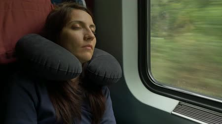 poduszka : Woman is sleeping in the car while travelling by train and having an inflatable neck pillow for sleep. Wideo