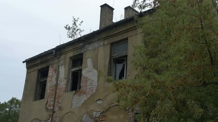 image house : Abandoned desolated house with broken windows and ruined walls, on grey sky.