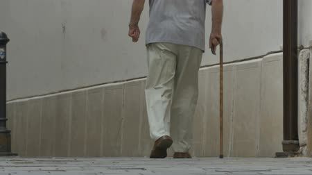 yorgunluk : Old man walking with cane along an alley in a sunny day. Stok Video