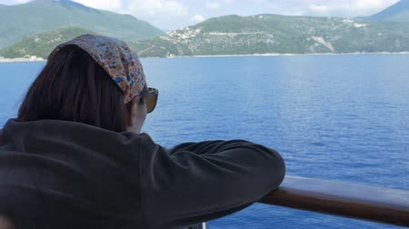 olhares : Tourist girl looking to shoreline while cruising by ship.