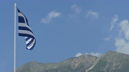 mirabello : Greece flag waving in  wind and mountains in the background. Stock Footage
