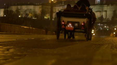 hackney carriage : A night carriage passing over the cobblestone street in Prague city.