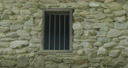 abandonar : Zoom into a mysterious window on stone wall. Stock Footage