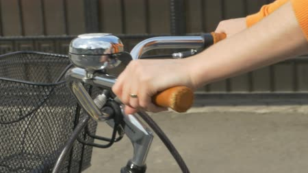 brake : Female ringing the bicycle bell ounted in the handlebar for announcing her presence in traffic.