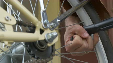 repairer : Manually inflating a bicycle tyre by air pump.
